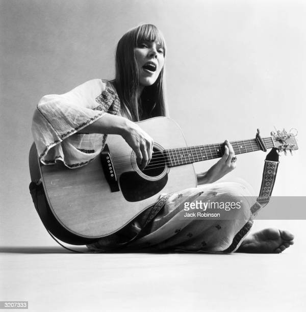 Portrait of American musician Joni Mitchell seated on the floor and playing acoustic guitar This image was from a photo shoot for the fashion...
