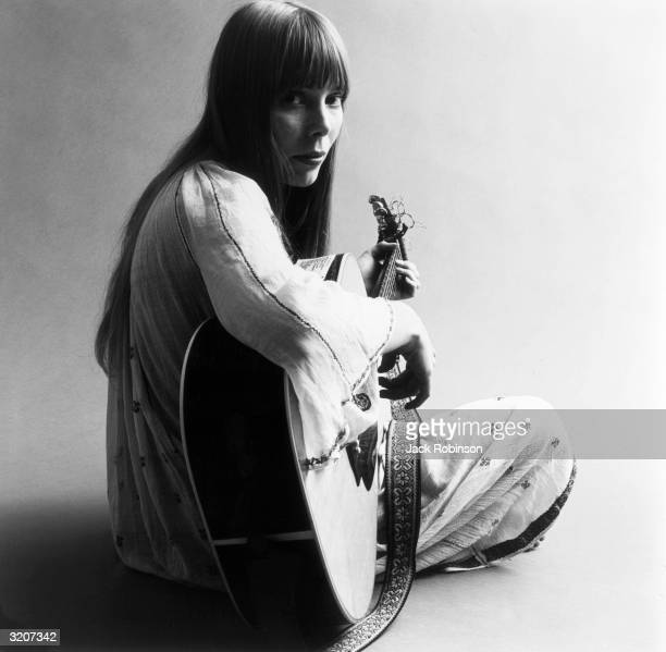 Portrait of American musician Joni Mitchell seated on the floor playing acoustic guitar This image is from a shoot for the fashion magazine Vogue...