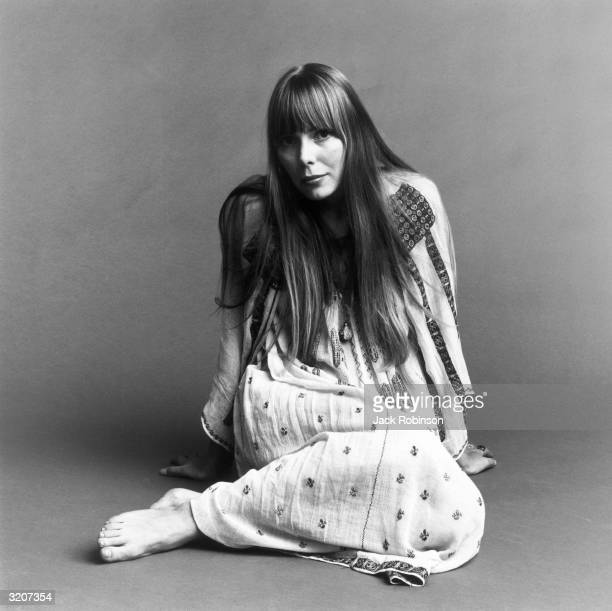 Portrait of American musician Joni Mitchell seated on the floor with her hands behind her This image is from a shoot for the fashion magazine Vogue...