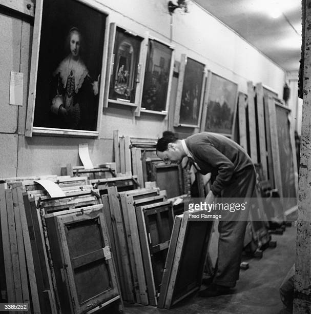 Sir Kenneth Clark director of the National Gallery examines paintings to see if they need to be returned from their wartime place of safety in Wales...