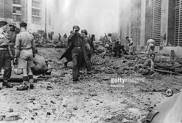 American and British soldiers in a Naples street helping victims injured by a German planted delayed action bomb.