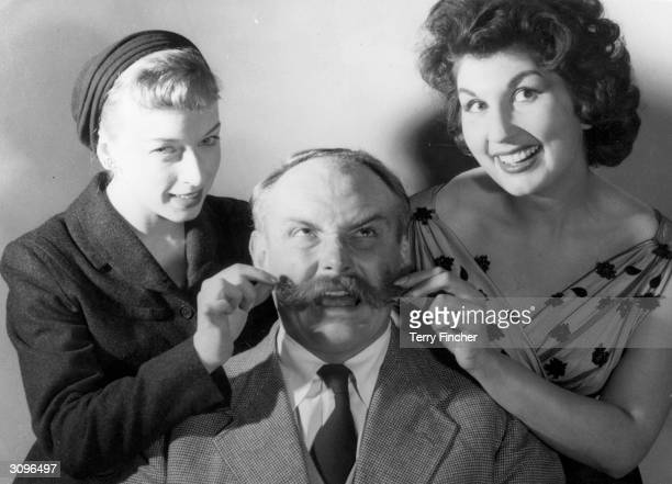 Comic actor Jimmy Edwards is having his moustache twirled by musical comedy actress June Whitfield and singer Alma Cogan June and Alma are taking...