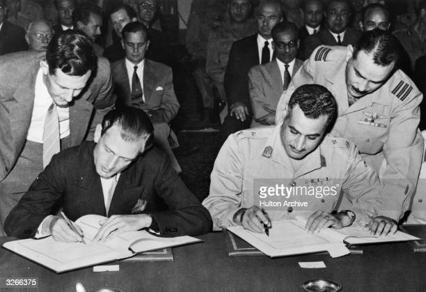 Egyptian Prime Minister Gamal Abdul Nasser and British minister of state Anthony Nutting signing the AngloEgyptian Agreement in the Pharaonic Hall of...