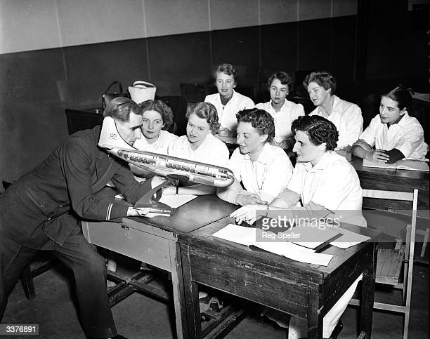 Instructor Tom Harmer shows the layout of a BOAC Stratocruiser to a class of trainee air stewardesses at a BOAC Catering Training School near Heston...