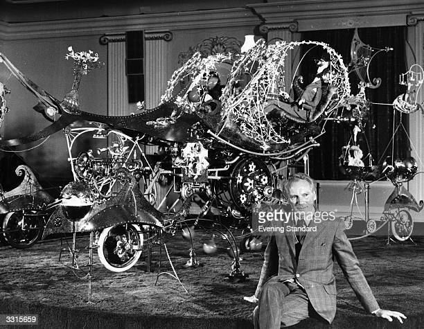Cartoonist and designer of quirky mechanical displays Rowland Emett, with his 'car of the future' at Grosvenor House, London.