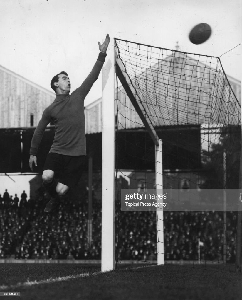 Hull City's goalkeeper makes a spectacular leap to push the ball over the bar during their match against Woolwich Arsenal at Highbury.