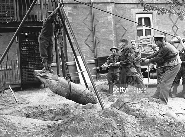 Lieutenant R Davies of the Bomb Disposal Unit stands on a 1200 pound time bomb as members of his unit hoist it up from the grounds of the German...