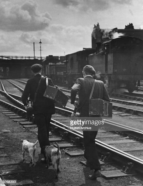 Railway rat catchers walk along the track