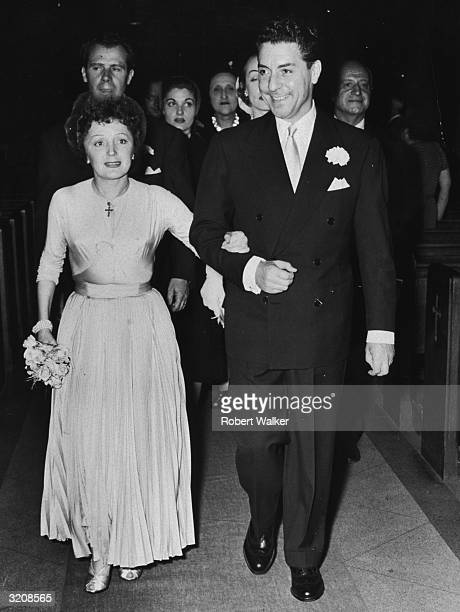 French cabaret singer Edith Piaf and her husband singer and composer Jacques Pills walking up the aisle at their wedding ceremony at St Vincent de...