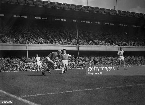 Arsenal footballer Victor Groves challenging the Manchester City's German goalkeeper Bert Trautmann for the ball during a game at Highbury