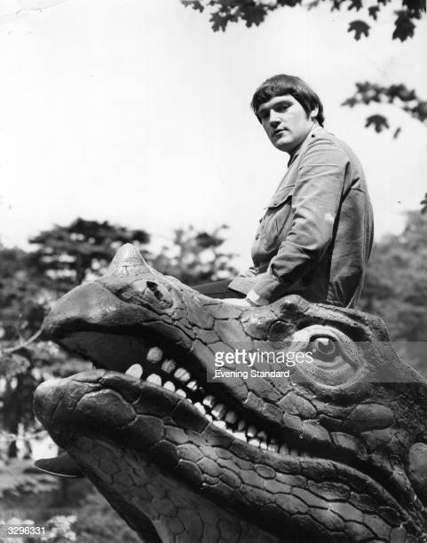 British jazz rock organist Brian Auger whose group Trinity currently includes vocalist Julie Driscoll perches calmly on the head of a model dinosaur