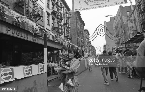 New York City A mother carries her young child down the streets of Little Italy during the annual Feast Of San Gennaro Festival