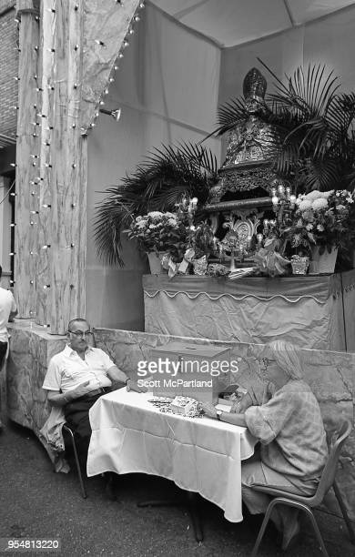 New York City A senior couple sits and watches over a donation box in front of the San Gennaro statue in Little Italy