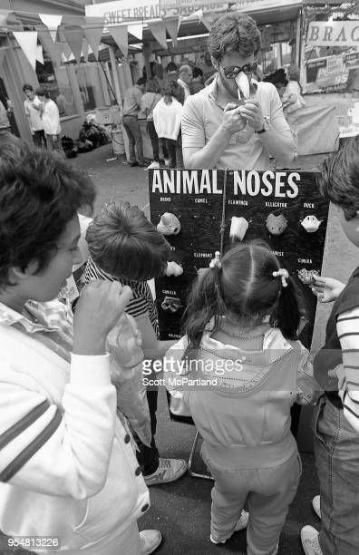 New York City A street vendor lights a cigarette as children look at the items he has for sale at the annual Feast Of San Gennaro Festival in Little...