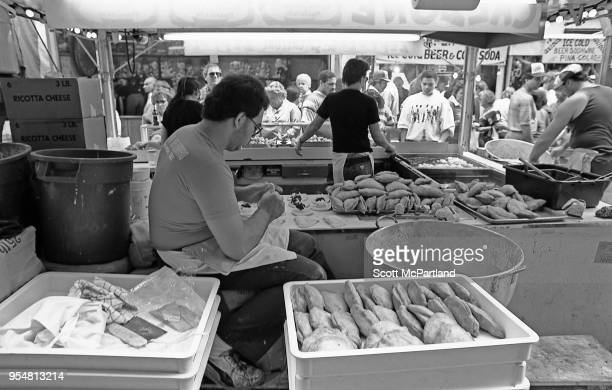 New York City A vendor prepares food while his partner serves customers during the annual Feast Of San Gennaro Festival in Little Italy