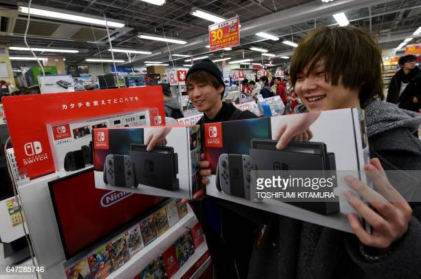 Year-old Hiroki Higuchi and his friend Tomohiro Yagi, 20 show off their newly purchased Nintendo Switch game consoles at a shop in Tokyo on March 3,...