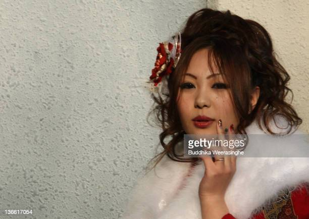 A 20yearold Japanese woman smokes a cigarette during the Coming of Age Day at Cultural Hall on January 9 2012 in Himeji Japan The event involves...