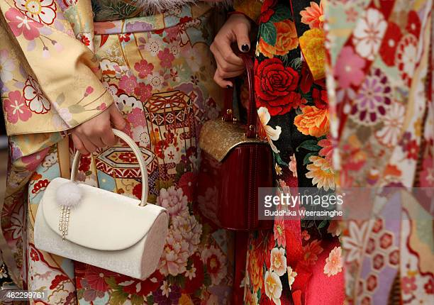 Year-old Japanese women dressed in traditional clothes and hold bag during the Coming of Age Day ceremony at Cultural Hall on January 13, 2014 in...
