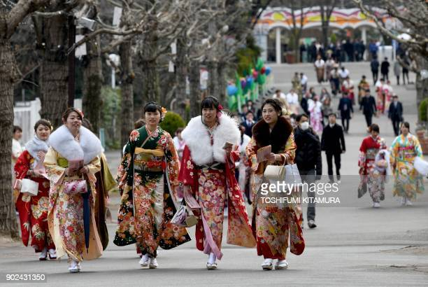 """Year-old women wearing kimonos walk towards their """"Coming-of-Age Day"""" ceremony at the Toshimaen amusement park in Tokyo on January 8, 2018. Dazzling..."""