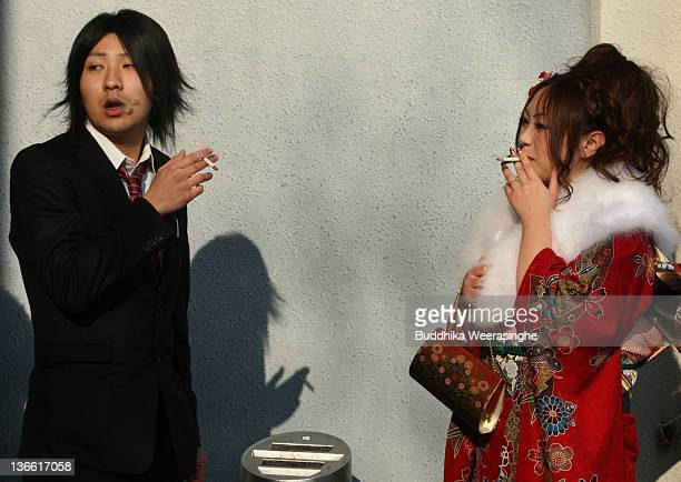 A 20yearoldJapanese man and woman smoke a cigarette during the Coming of Age Day at Cultural Hall on January 9 2012 in Himeji Japan The event...