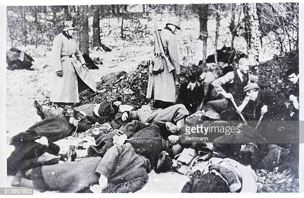 Polish civilian prisoners are shown digging a grave for ten of their fellows who had just been executed by a German firing squad The bodies lie about...