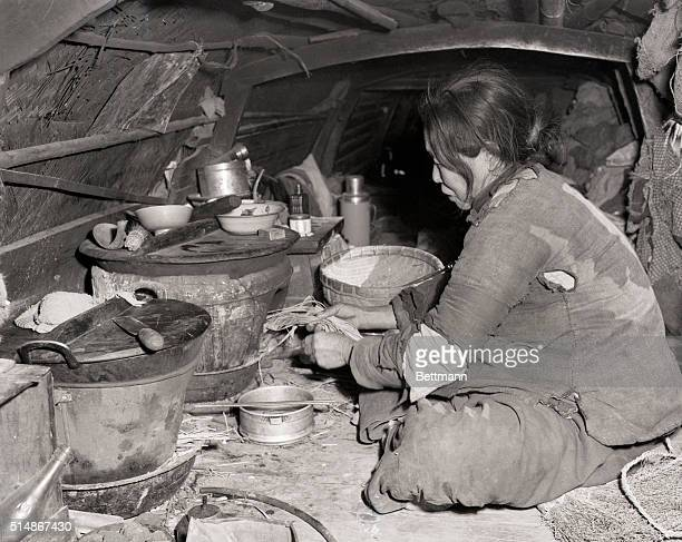 2/1/1949Shanghai China This poor woman a refugee from warwracked north China now living on a sampan on Shanghai's Soochow Creek lights her stove in...