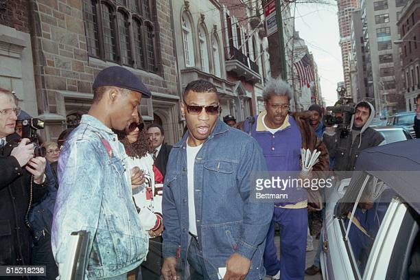2/12/1990New York New York Just back from Tokyo where he was kayoed by James Douglas Mike Tyson is followed by promoter Don King as they leave King's...