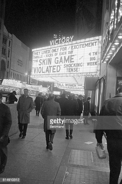 2/13/1967New York NYA crowd of men gather under a neonlighted marquee to look over the movie stills advertising a sex film at one of the several...
