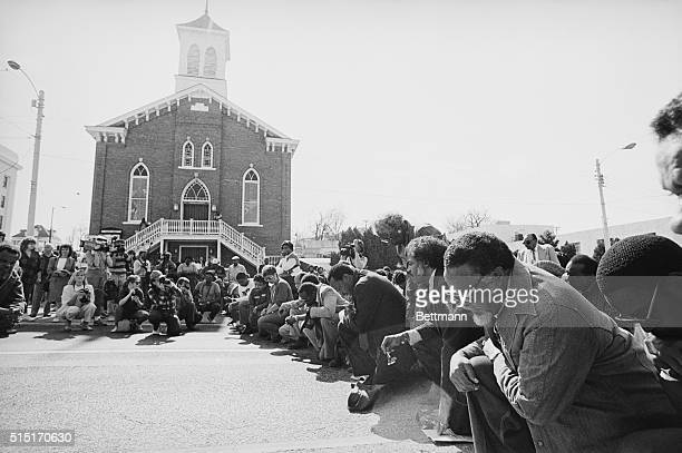 2/14/1987Montgomery AL Rev Hosea Williams Atlanta City Councilman kneels in prayer in front of the Dexter Avenue King Memorial Church along with an...
