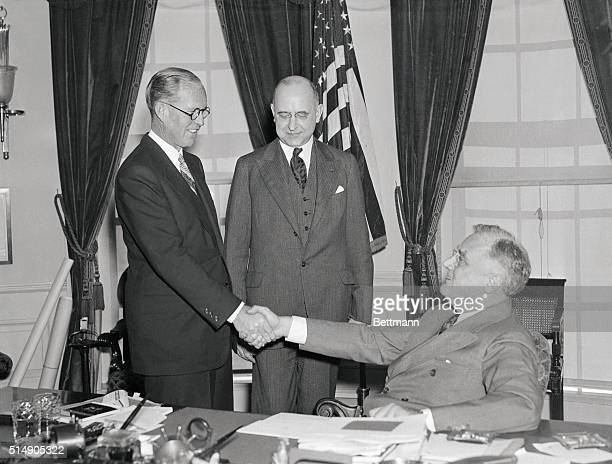 Washington, D.C.: With President Roosevelt looking on, Joseph P. Kennedy, former Chairman of the US Maritime Commission, is pictured above , being...