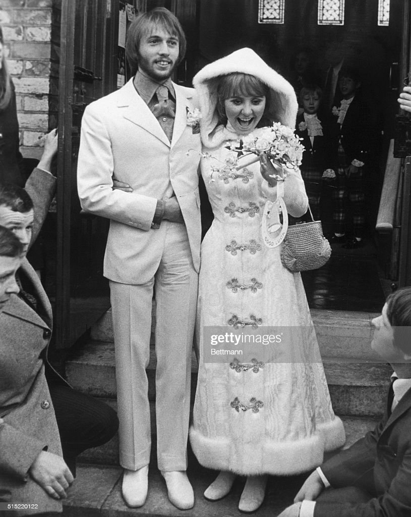 Gerrards Cross, England-Pop singer Lulu (Marcia McDonald McLaughlin Lawrie) and Australian singer Maurice Gibb of the Bee Gees pop group, leave the parish church following their wedding. Lulu wears a white, floor-length, mink-trimmed, hooded coat over a mini-dress. Maurice is clad in a white suit with a royal blue shirt.