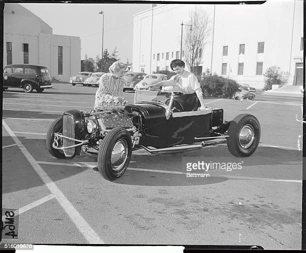 2/18/53Oakland California LR Margaret Page and Pat Lauderback tinker with the workings of this beautiful 'hot rod' at the National Roadster Show...