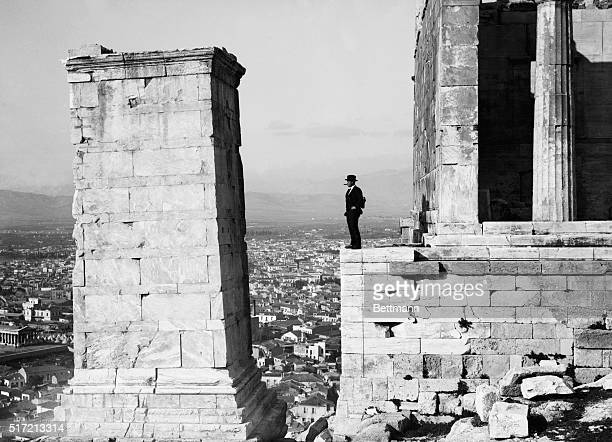 Athens, Greece: Man stands atop the Acropolis smoking a cigar and looking at the view of Athens.
