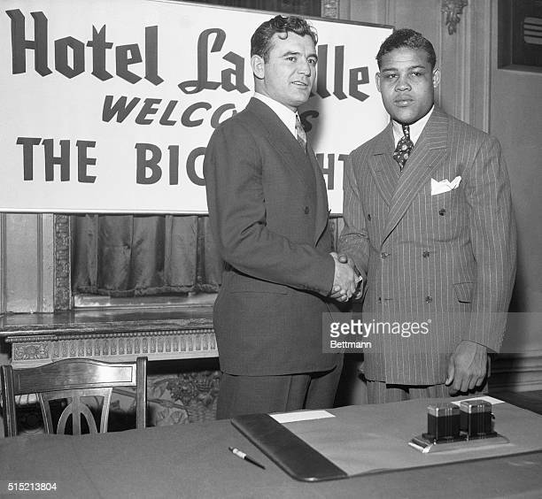 2/19/1937Chicago IL James Braddock heavyweight champion of the world and Joe Louis the challenger are shown shaking hands after they had signed for...