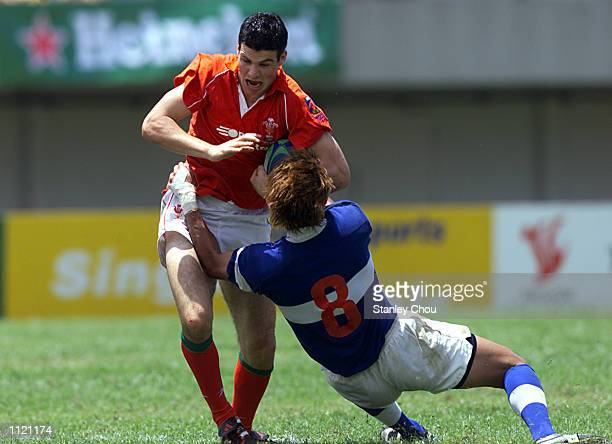 Mike Phillips of Wales is stopped by ChihWei Wu of Chinese Taipei during the Singapore Sevens Shield quarterfinals between Wales and Chinese Taipei...