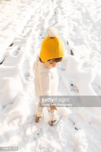 a 21-month-old toddler girl wearing a yellow hat & cream-colored sweater, walking and discovering the fluffy white snow for the first time on christmas day - beige shoe stock pictures, royalty-free photos & images