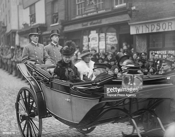 Queen Mary with Prince George and Henry and Princess Mary drive down a street in Windsor in an open carriage on St George's Day
