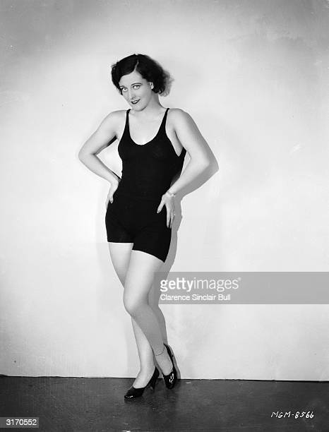 American actress Joan Crawford wearing a dark swimsuit with high heeled shoes
