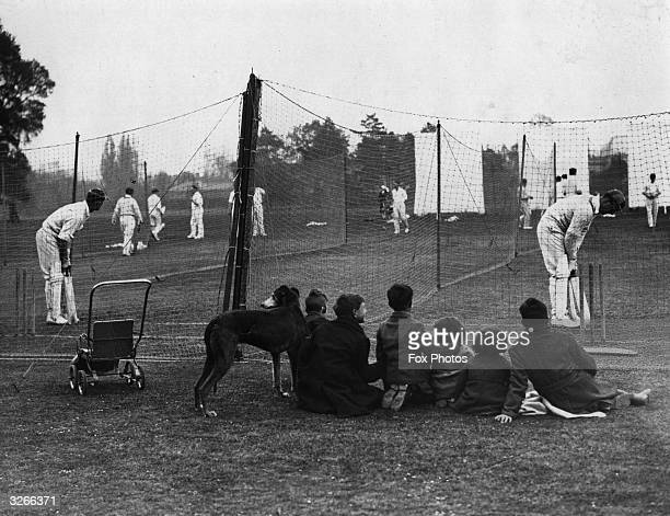 A group of young children watch Oxford University cricketers at practice in the nets