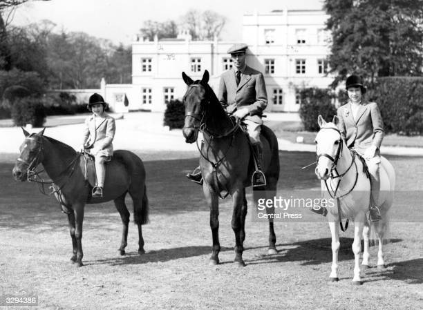 From left Princess Margaret Rose King George VI and Queen Elizabeth II as Princess Elizabeth The family is riding at Windsor Great Park on Princess...