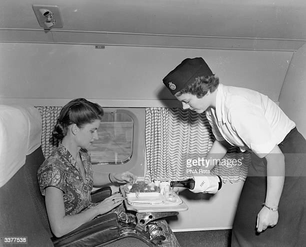 E Courtney a member of the cabin crew serving luncheon to a passenger on board the world's first jet airliner service The Comet flight is bound for...