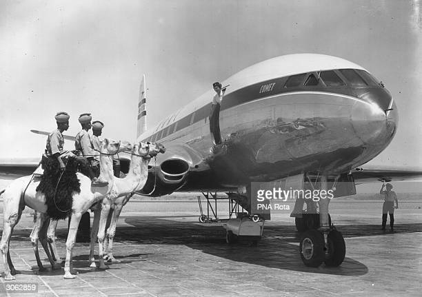 Three Sudanese policemen mounted on camels are greeted by air stewardess E Courtney when the world's first jet airliner service arrives at Khartoum...