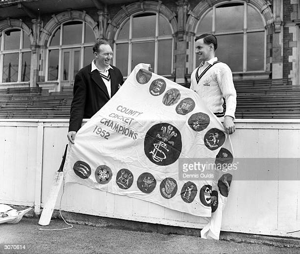 Surrey Captain W S Surridge and England and Surrey batsman Peter May hold the Championship pennant presented to Surrey by the previous champions...