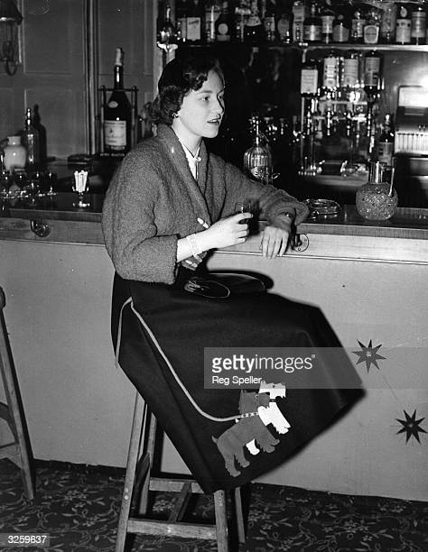 Miss Jennifer Hall enjoying a drink at the bar of the 'Bear Hotel' Maidenhead She is fashionably dressed in a poodle cloth jacket and felt skirt...