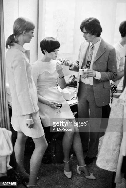 English fashion designer Ossie Clark offers a light to the model Judy Guy Johnson while Patti Boyd a model and the wife of Beatle George Harrison...