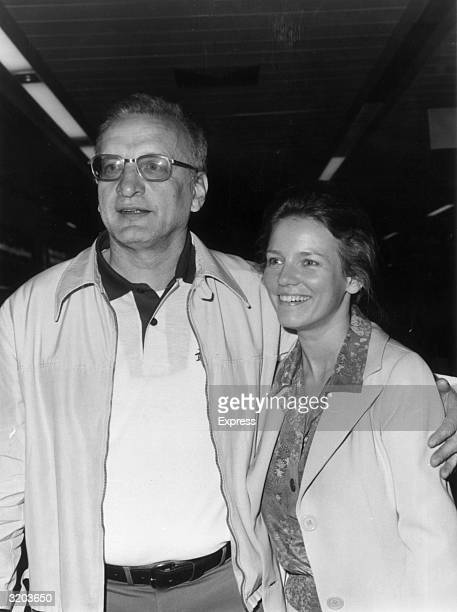 American actor George C Scott holds his around his wife Trish Van Devere at Heathrow Airport London England The couple were in England to costar in...