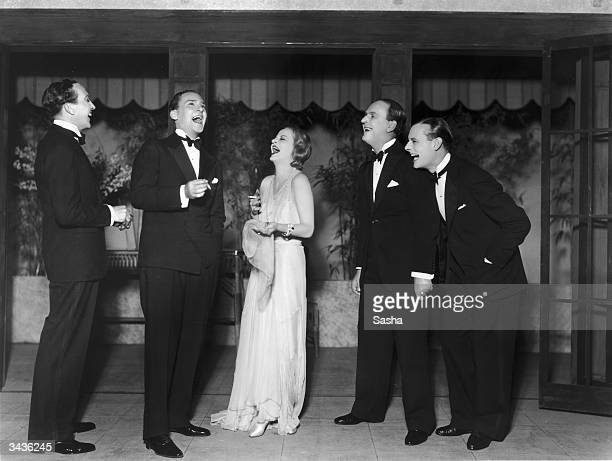 A group of actors amongst them Tallulah Bankhead are doubled over with hysterical laughter in a scene from the play 'Let Us Be Gay' at the Lyric...