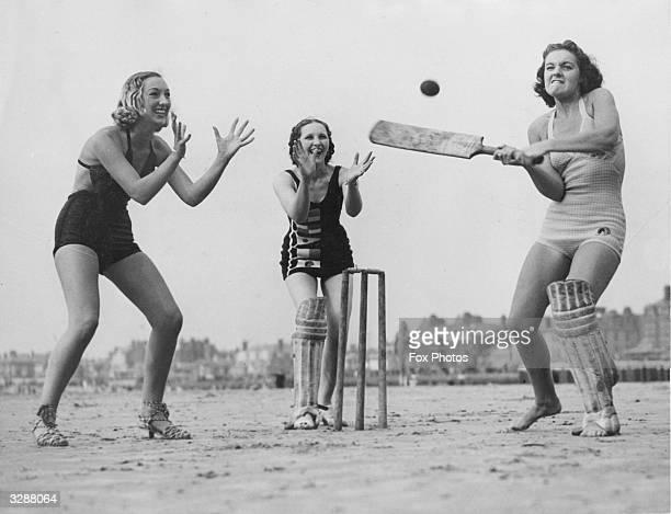 Three girls enjoying a game of cricket on the beach at Blackpool Lancashire