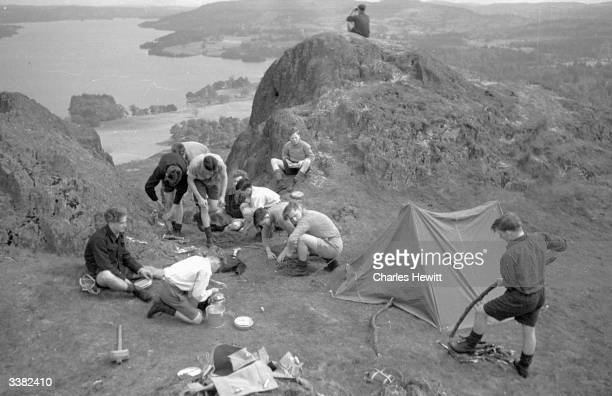 Teenage boys, on holiday from their jobs in factories and mines, pitching a tent above Lake Windermere, in the Lake District. The boys stay at...