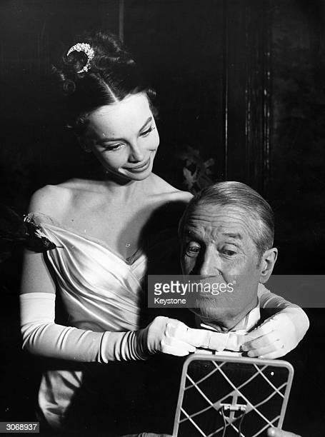 Leslie Caron arranges Maurice Chevalier's bow tie in a scene from the film 'Gigi' based on a novel by Colette.